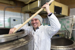 Production of cheese in dairy, worker cheese mixes Royalty Free Stock Photography