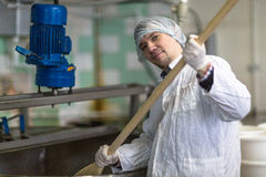Production of cheese in dairy, worker cheese mixes Royalty Free Stock Photos