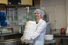 Production of cheese in dairy, worker with forms Royalty Free Stock Photo