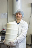 Production of cheese in dairy, worker with forms Royalty Free Stock Image