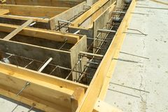 Production of the concrete base under the house with use of a removable timbering. stock image