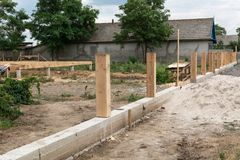 Concrete foundation for fence. Production of the concrete base for a wooden fence. Production of the concrete base for a wooden fence. Concrete foundation for royalty free stock image