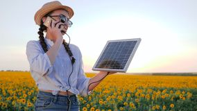 Production of energy, woman in backlight talk phone and keep solar battery tracking sun to charge battery. Girl speaks by mobile phone and holds solar panel in stock video footage
