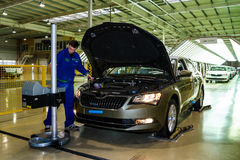 Production of Škoda Kodiaq began in Ukraine. Solomonovo, Ukraine - March 9, 2017. The mechanic adjusts the headlights of the Octavia car in the workshop of the Royalty Free Stock Photo