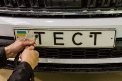 Production of Škoda Kodiaq began in Ukraine. Solomonovo, Ukraine - March 9, 2017. The mechanic fastens the license plate on the Octavia car for a test drive in Stock Photos