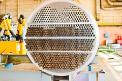 Production of a large tube bundle for a shell-and-tube heat exchanger in an industrial production room of a shop with equipment. At an oil refinery royalty free stock photo