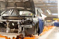 The production line for the assembly of new vehicles. Production of machines in the factory stock photo