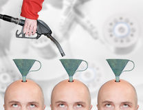 Production line for education or brainwashing. Hairless men's heads with funnels and fuel nozzle. Production line for education or brainwashing royalty free stock photo