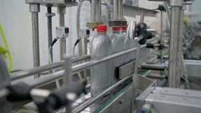Production machine fix red caps on plastic bottles on conveyor at motor oil factory stock video footage