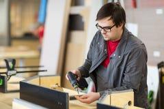 Assembler with screwdriver making furniture Royalty Free Stock Image