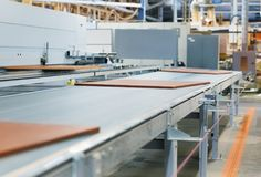 Chipboards on conveyer at furniture factory. Production, manufacture and woodworking industry concept - chipboards processing on conveyer at furniture factory royalty free stock images