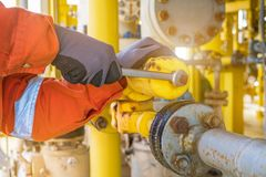 Production operator adjusting pressure regulator of instrument gas supply system at offshore oil and gas wellhead remote platform royalty free stock photos