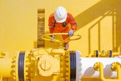 Production operator opening valve on offshore oil and gas central processing platform.