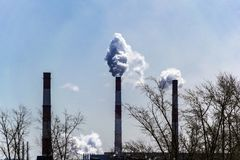 Production pipes pollute the clear sky. Production pipes smoke against a clear sky royalty free stock images