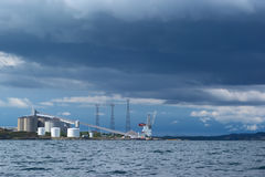Production Plant on the Norwegian Coast. Production plant on the West-Norwegian coast photographed from the sea with dark clouds in the sky Stock Photo