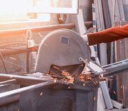 Production of pvc windows, worker cuts a metal profile on a circular saw, close-up, hand, sun stock photos