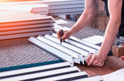 Production of PVC windows, the worker records dimensions on the profile of the frame pvc, felt pen arm royalty free stock photography