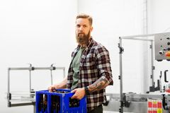 Man with bottles in box at craft beer brewery. Production, small business and people concept - man with bottles in box at craft brewery or beer plant royalty free stock photo