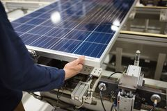 Production of solar panels, man working in factory. stock image