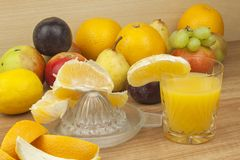 Production of summer fruit juices. Domestic fresh orange juice in a glass jar on a wooden table. Stock Images