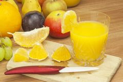 Production of summer fruit juices. Domestic fresh orange juice in a glass jar on a wooden table. Royalty Free Stock Image