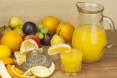 Production of summer fruit juices. Domestic fresh orange juice in a glass jar on a wooden table. Royalty Free Stock Photo