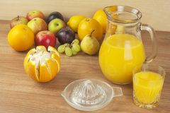 Production of summer fruit juices. Domestic fresh orange juice in a glass jar on a wooden table. Royalty Free Stock Photos