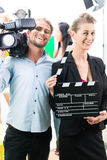 Production team with camera and take clap on film set or studio Royalty Free Stock Images