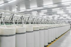 Production of threads in a textile factory. Machinery and equipment in the workshop for the production of thread, overview. interior of industrial textile stock photo