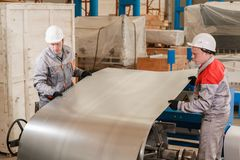 Production of ventilation and drainpipe. Workers adjusts the machine in the warehouse. the production of ventilation and royalty free stock image