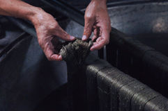 Production and weaving of carpets and fabrics. Painting threads and yarns. male hands paint the cloth in the trough stock photo