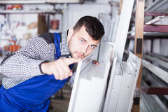 Production worker with PVC windows. Positive production worker in coverall with different PVC windows and doors Stock Photo
