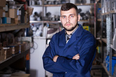Production worker in uniform displaying his workplace. At workshop Royalty Free Stock Image