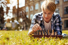 Productive admirable guy making important move. Strategic thinker. Handsome inspiring focused men using chess for keeping his mind in shape and developing his Royalty Free Stock Images