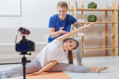 Cheerful bloggers doing sport exercises in front of the camera Royalty Free Stock Photos