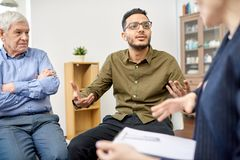 Productive Problem Discussion at Group Therapy Session. Handsome mixed-race patient suffering from depression talking to psychologist while participating in stock photo