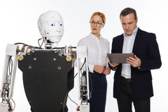 Productive serious scientists studying robots abilities. Latest development. Talented strategic savvy colleagues working on modern lab and applying some settings Royalty Free Stock Photos