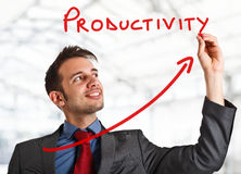 Productivity. Friendly businessman writing the word Productivity and a rising arrow Royalty Free Stock Photos