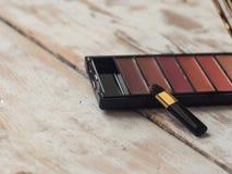 Producto del labio del maquillaje en fondo de madera ligero con el copyspace Imagen de archivo libre de regalías