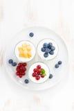 Producto dietético - yogur del surtido con las bayas frescas en vidrio Fotografía de archivo