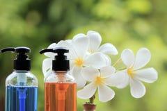 Producto, ducha, champú, loción y Frangipani o plumer del cuidado del cuerpo foto de archivo