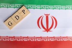 Producto interno bruto o GDP de Irán en letras de molde de madera en la bandera de Irán fotos de archivo