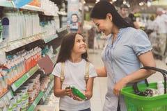 Producto lácteo de compra feliz de la muchacha y de la mujer Fotografía de archivo libre de regalías