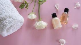 Producto para el cuidado de la piel orgánico y flores delicadas en fondo rosado Productos cosméticos sanos almacen de metraje de vídeo