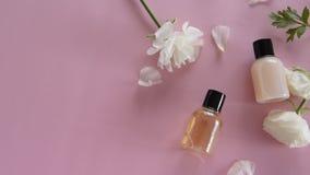 Producto para el cuidado de la piel orgánico y flores delicadas en fondo rosado Productos cosméticos sanos metrajes