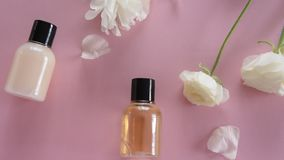 Producto para el cuidado de la piel orgánico y flores delicadas en fondo rosado Productos cosméticos sanos almacen de video