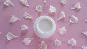 Producto para el cuidado de la piel orgánico y pétalos delicados de la flor en fondo rosado Productos cosméticos sanos metrajes