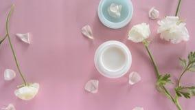 Producto para el cuidado de la piel orgánico y pétalos delicados de la flor en fondo rosado Productos cosméticos sanos almacen de metraje de vídeo