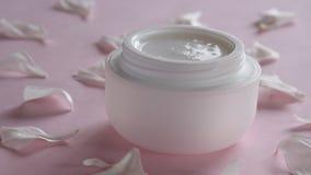 Producto para el cuidado de la piel orgánico y pétalos delicados de la flor en fondo rosado Productos cosméticos sanos almacen de video