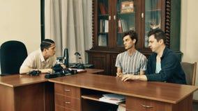 Productor cinematográfico en hablar enojado de la camisa blanca con los trabajadores de la oficina sobre el guión metrajes